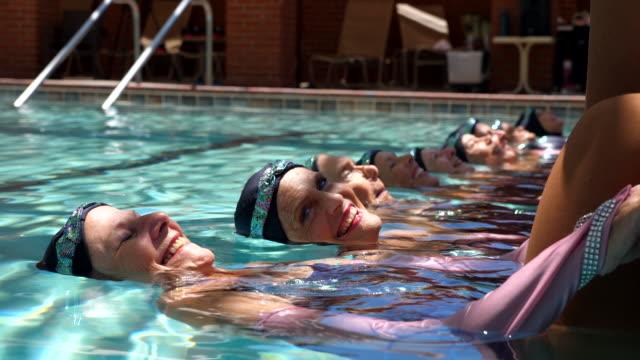 vidéos et rushes de cu smiling senior female synchronized swim team posing on edge of pool during routine - octogénaire et plus