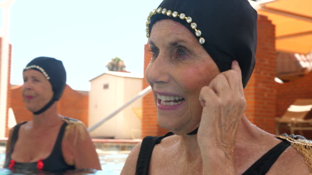 cu smiling senior female synchronized swimmer waving to camera after practicing routine in pool - wassersport stock-videos und b-roll-filmmaterial