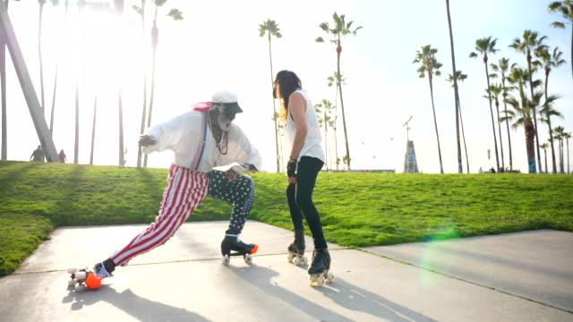 ms smiling senior friends roller skating together in park - lingerie stock videos & royalty-free footage