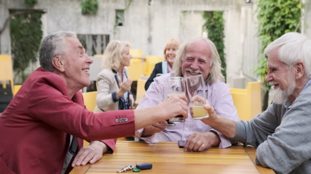 Smiling Senior Male Friends Toasting with Beer at Cafe