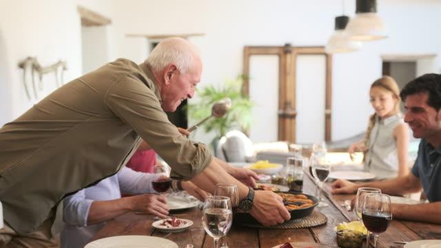 vídeos y material grabado en eventos de stock de hombre senior sonriente entregando pan de paella a mesa de comedor - cultura mediterránea