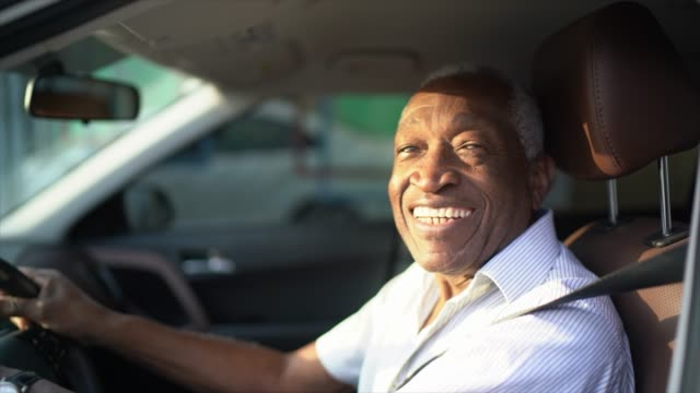 vídeos de stock e filmes b-roll de smiling senior man driving a car and looking at camera - brazilian ethnicity