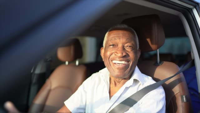 smiling senior man driving a car and looking at camera - pardo brazilian stock videos & royalty-free footage