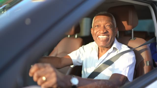 smiling senior man driving a car and looking at camera - chauffeur stock videos and b-roll footage