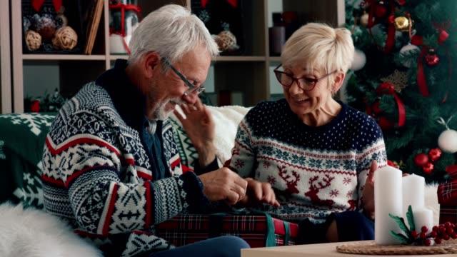 vidéos et rushes de homme aîné de sourire ouvrant un cadeau de noel sa femme lui a donné - décoration de noël