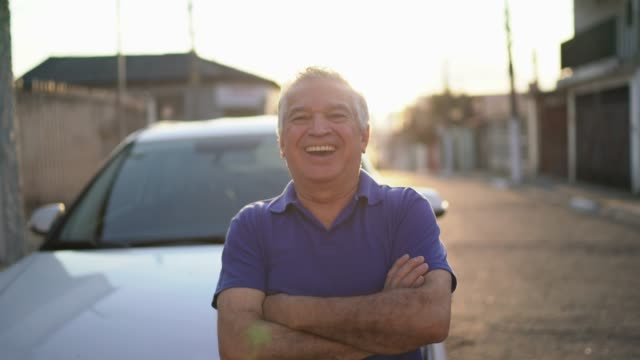 vídeos de stock e filmes b-roll de smiling senior man standing in front of his car - brazilian ethnicity