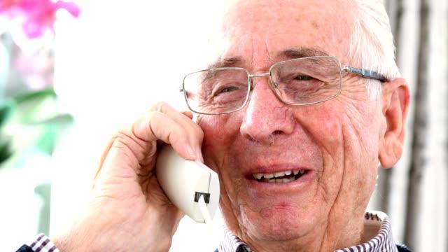 Smiling Senior Man Talking On Telephone At Home