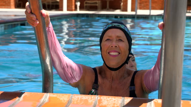 cu smiling senior synchronized swimmer preparing to exit pool after routine - caucasian appearance stock videos & royalty-free footage