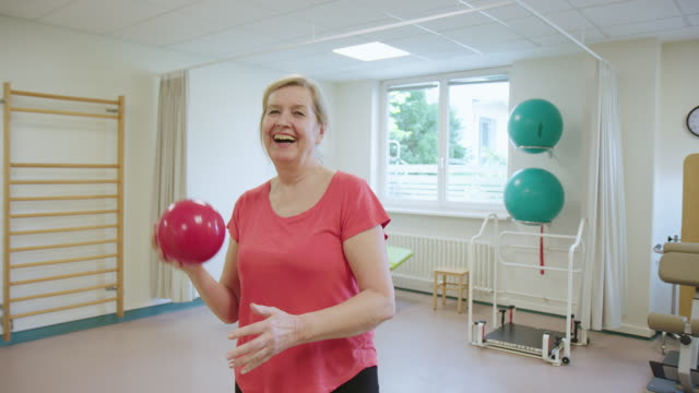 smiling senior woman exercising with fitness ball - rehabilitation center stock videos & royalty-free footage