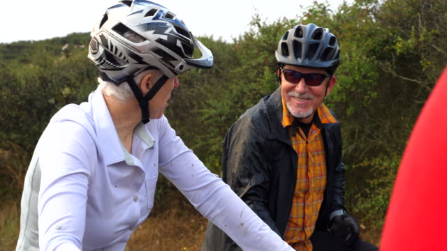 vidéos et rushes de ms smiling senior woman in discussion with friends while resting during mountain bike ride - senior dynamique