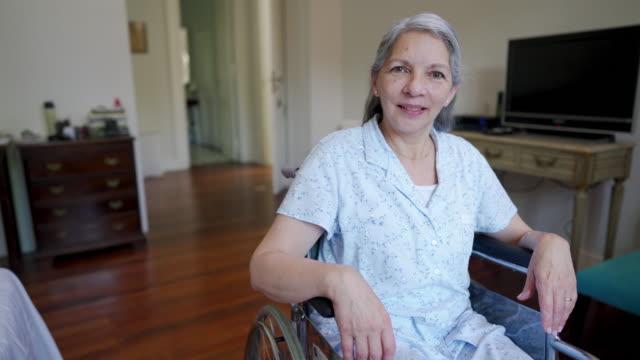 smiling senior woman in wheelchair in nursing home - retirement community stock videos & royalty-free footage