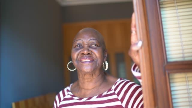vidéos et rushes de femme aîné de sourire regardant par la fenêtre contemplant et pensant à la maison - brésilien
