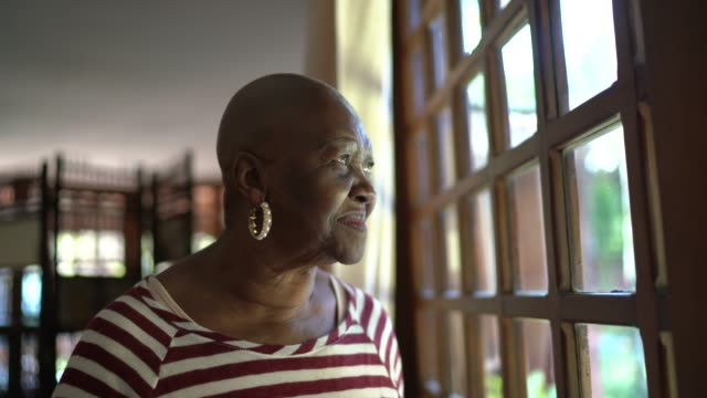smiling senior woman looking through window contemplating and thinking at home - completely bald stock videos & royalty-free footage