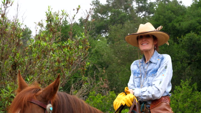 cu smiling senior woman on early morning horseback ride - cowboy hat stock videos & royalty-free footage