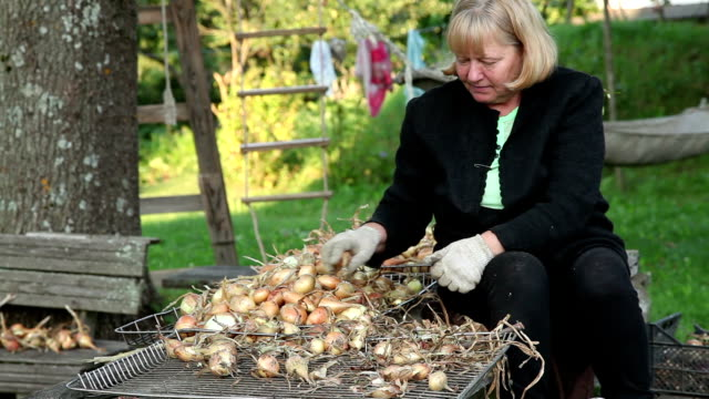 Smiling senior woman sorting onions at the table