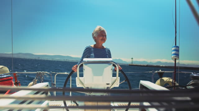 Smiling senior woman steering boat in vacation