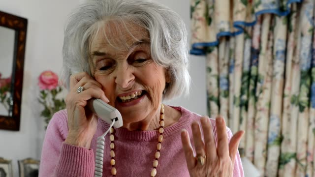 Smiling senior woman talking on phone at home