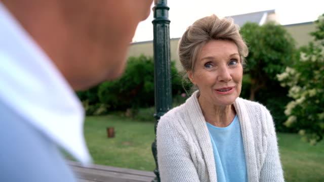 Smiling senior woman talking with man in yard