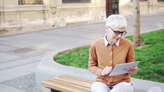 Lächelnde Seniorin mit digitalem Tablet.