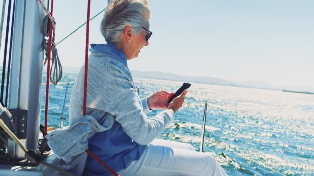 vídeos de stock, filmes e b-roll de mulher senior sorridente usando telefone inteligente no barco - riqueza