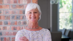 Smiling senior woman walks into focus looking to camera