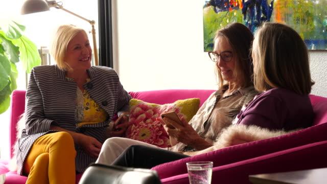 vídeos y material grabado en eventos de stock de ms smiling senior women hanging out on couch in living room - amistad femenina
