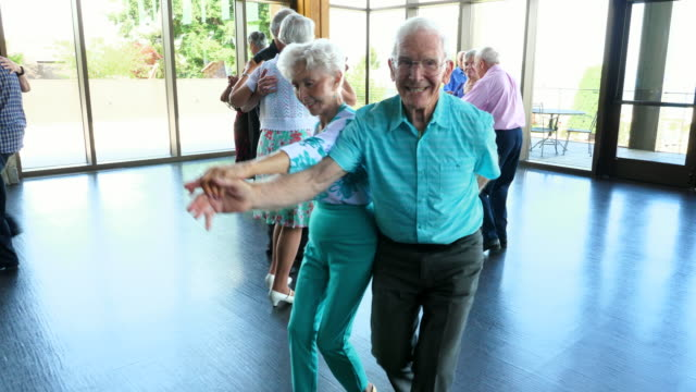 ms smiling seniors dancing in community center - älteres paar stock-videos und b-roll-filmmaterial