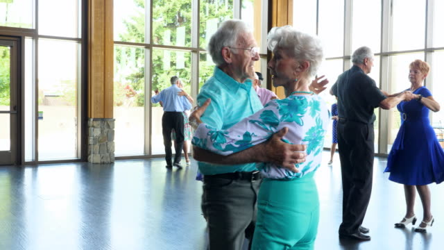TS Smiling seniors dancing together in community center