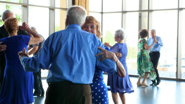 vídeos de stock, filmes e b-roll de pan smiling seniors dancing together in community center - 70 anos