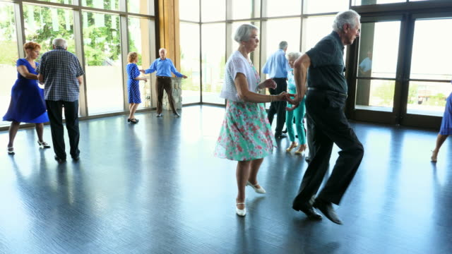 vídeos de stock, filmes e b-roll de ms smiling seniors dancing together in community center - active seniors