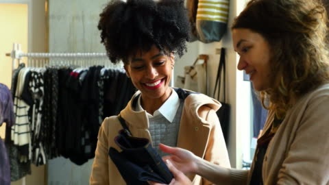 stockvideo's en b-roll-footage met ms smiling shop owner showing pair of jeans to customer in boutique - klanten georiënteerd