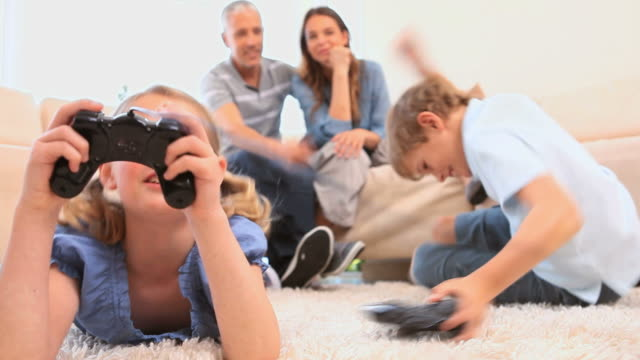 Smiling siblings playing video games