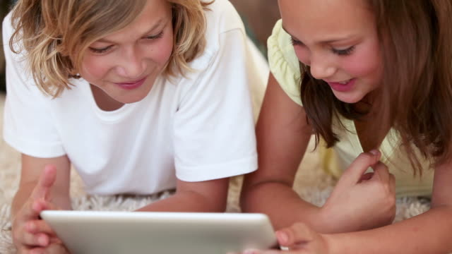 Smiling siblings using a tablet computer