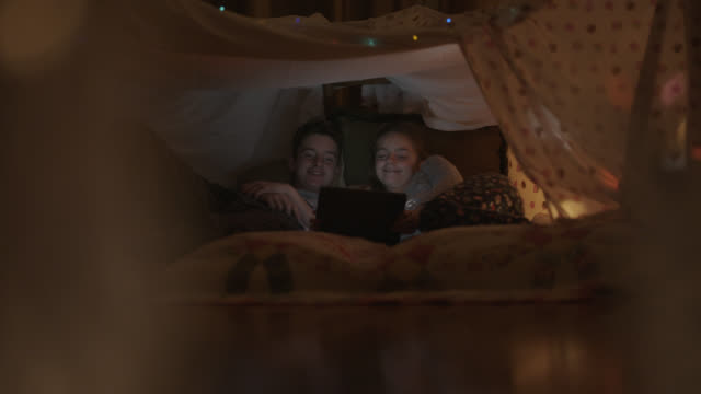 smiling siblings watch a movie while inside a pillow fort. - bed sheets stock videos & royalty-free footage