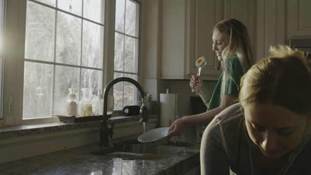 vidéos et rushes de smiling sisters washing dishes and singing to music in kitchen / highland, utah, united states - lave vaisselle