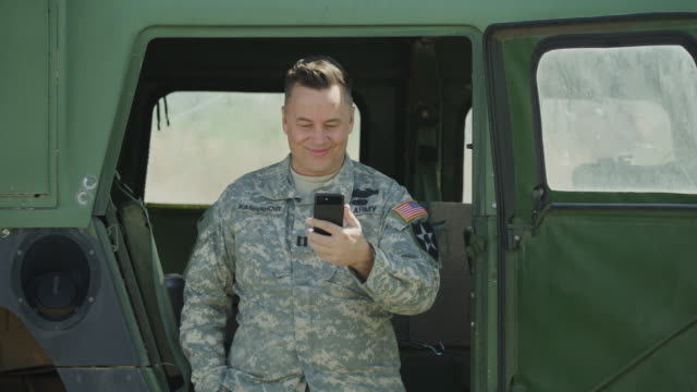 stockvideo's en b-roll-footage met smiling soldier standing near military vehicle video chatting on cell phone / lehi, utah, united states - militair uniform