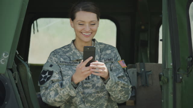 smiling soldier standing near military vehicle video chatting on cell phone / lehi, utah, united states - lehi stock videos & royalty-free footage