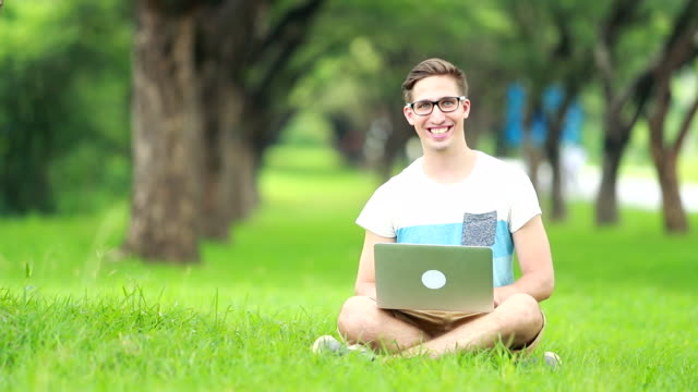 smiling student using laptop at the garden park , slow motion - fully unbuttoned stock videos & royalty-free footage