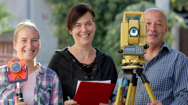 smiling surveyors with their equipment looking at camera - surveyor stock videos & royalty-free footage