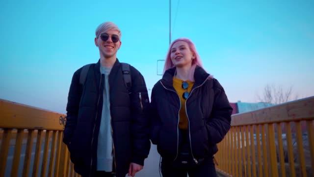 stockvideo's en b-roll-footage met glimlachend tiener paar in een wandeling - volgshot