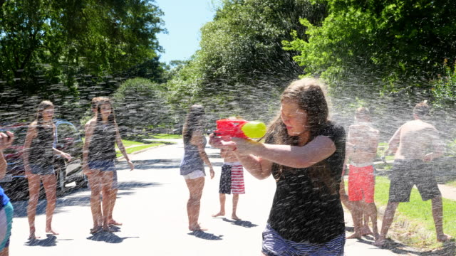 MS Smiling teen friends with squirt guns running through spray from fire hydrant on summer afternoon