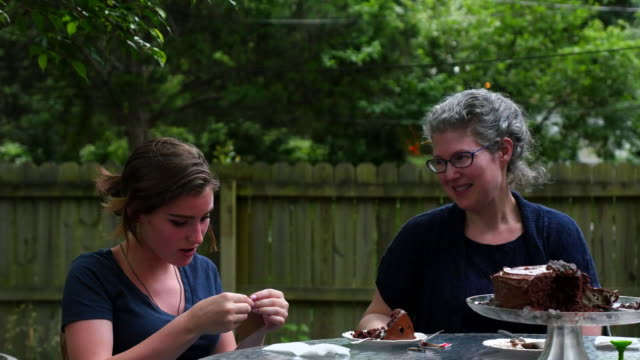 MS Smiling teenage daughter opening birthday gift from mother during celebration in backyard of home