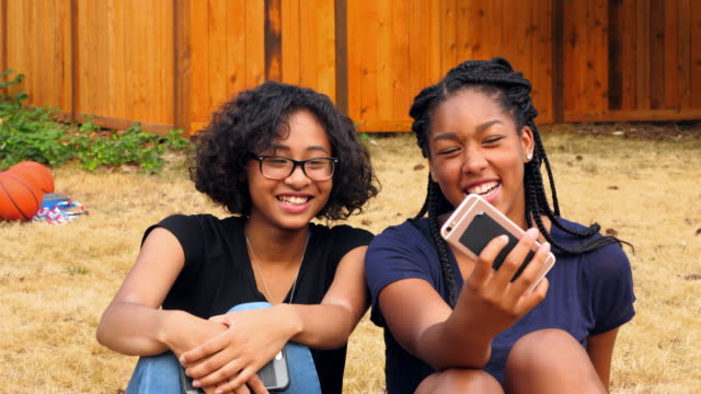 vidéos et rushes de ms smiling teenage friends taking selfie with smartphone on summer evening - 16 17 ans