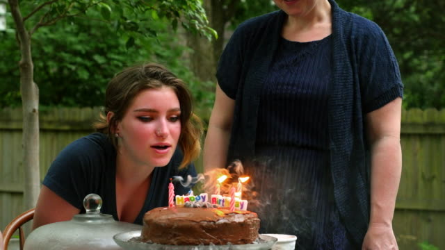 vidéos et rushes de ms tu pan smiling teenage girl blowing out candles on birthday cake at family party in backyard of home - anniversaire