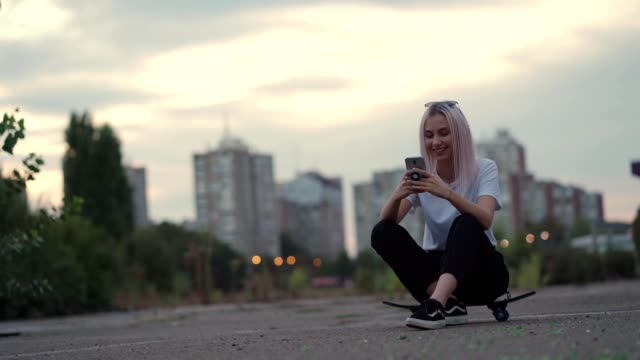 smiling teenage girl is texting message - city life stock videos & royalty-free footage
