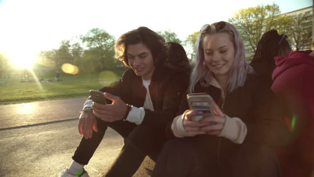 Smiling teenage girl looking at male friend using mobile phone while sitting on footpath