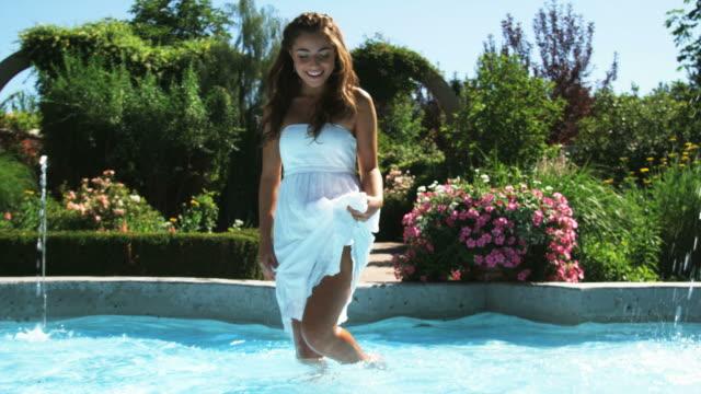 stockvideo's en b-roll-footage met slo mo ms smiling teenage girl (16-17) playing in fountain in summer garden, lehi, utah, usa - lehi
