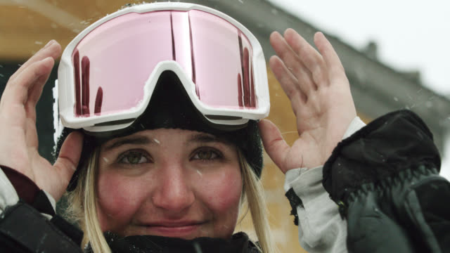 a smiling teenaged female snowboarder puts on her goggles in preparation of snowboarding on an overcast winter day - warm clothing stock videos & royalty-free footage