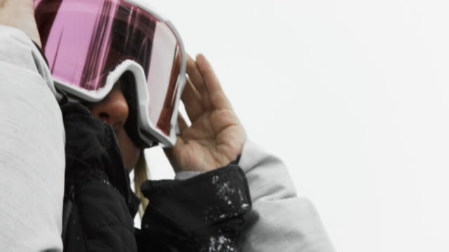 a smiling teenaged female snowboarder puts on her goggles in preparation of snowboarding on an overcast winter day - ski goggles stock videos & royalty-free footage