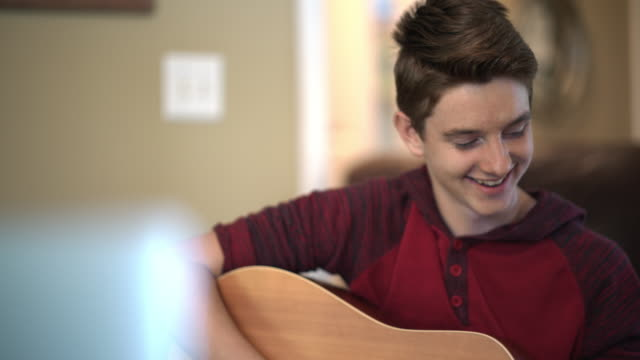 cu smiling teenager playing the acoustic guitar on a video call at home - one teenage boy only stock videos & royalty-free footage